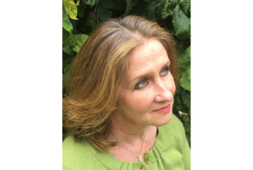Portrait of crime novel writer Sharon Bolton, high angle, looking off camera, greenery behind