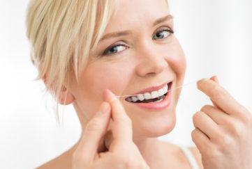 Blonde woman flossing her teeth