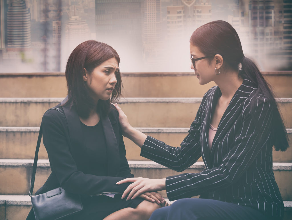 Businesswoman with hand on shoulder of colleague, consoling for help and support which her friend suffering