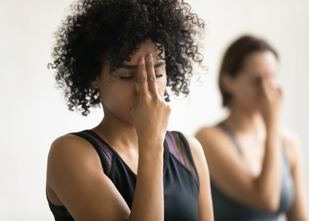 Woman in yoga class touches 2 fingers to her forehead during meditation