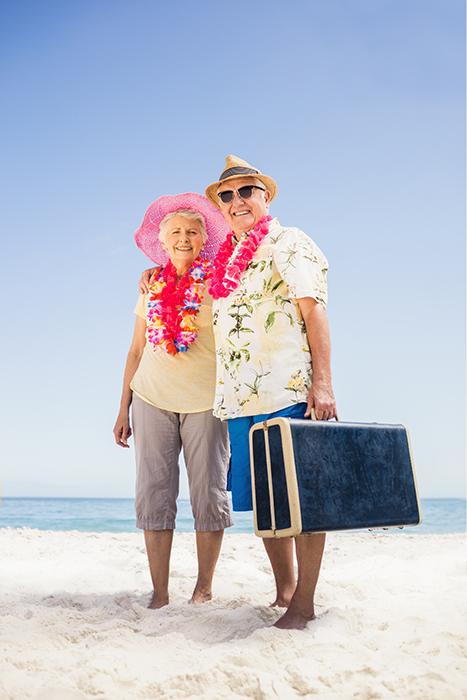 Senior couple holding suitcase on the beach