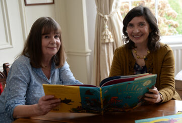 2 mature women looking at a large children's picture book, smiling