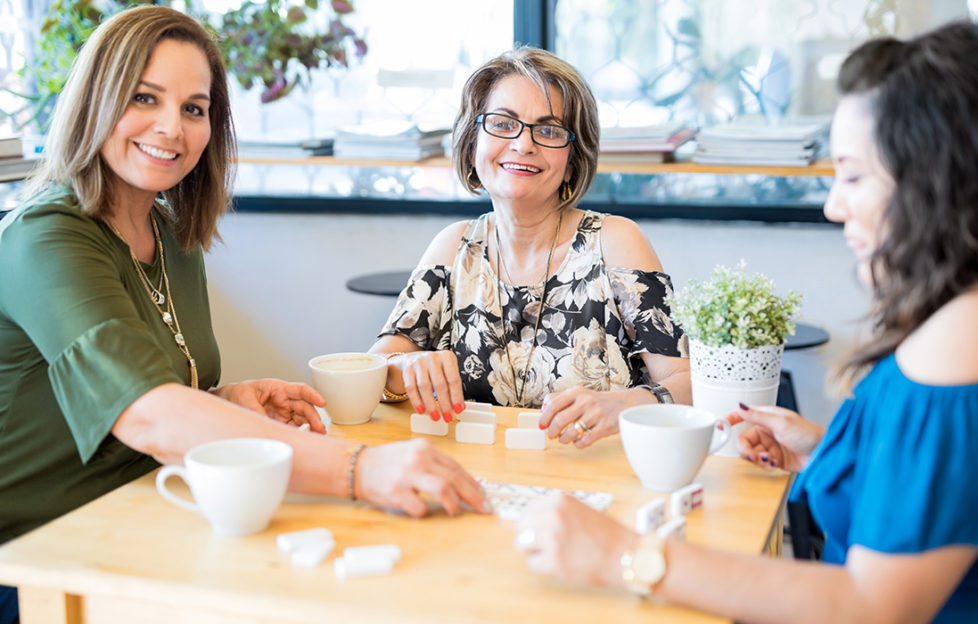 Portrait of cheerful women group playing dominoes and drinking coffee in a coffee shop; Loneliness week