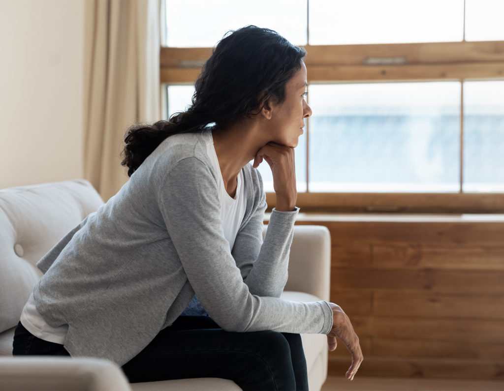 lonely woman looks out of window, loneliness awareness week Marmalade Trust
