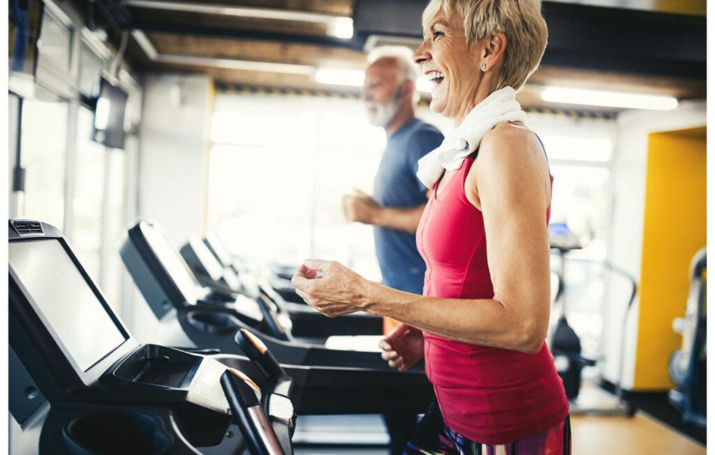 Senior people running in machine treadmill at fitness gym club;