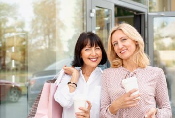 Two mature women having fun while doing shopping and drinking coffee. Pastime concept of mature people;