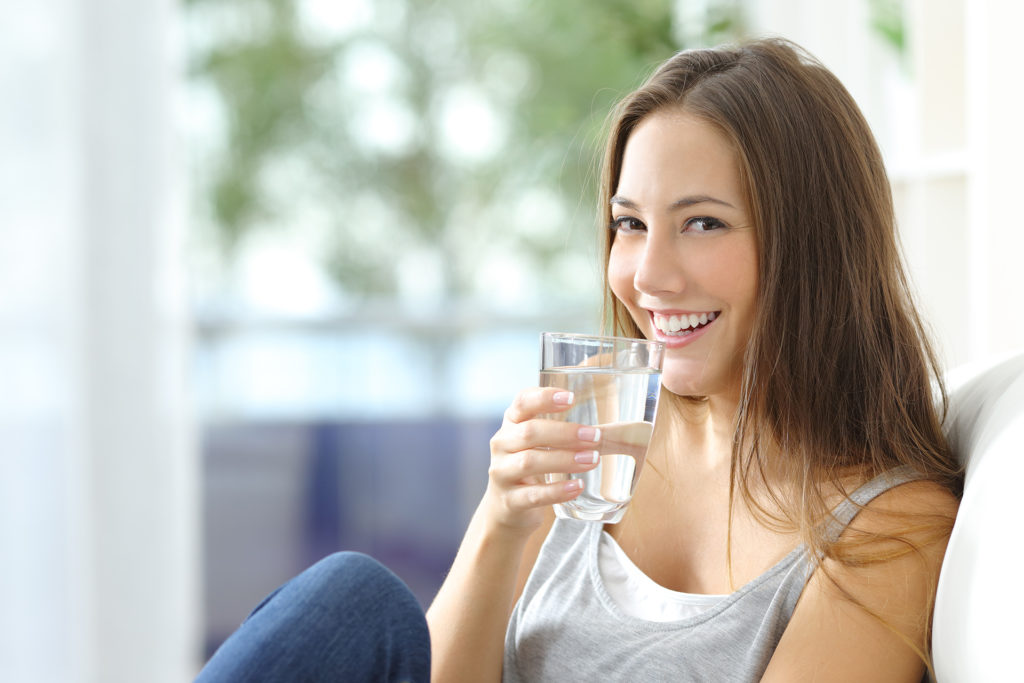 Girl drinking water sitting on a couch at home and looking at camera;