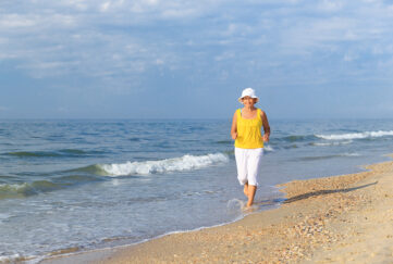senior woman jogging on sea beach at the morning;