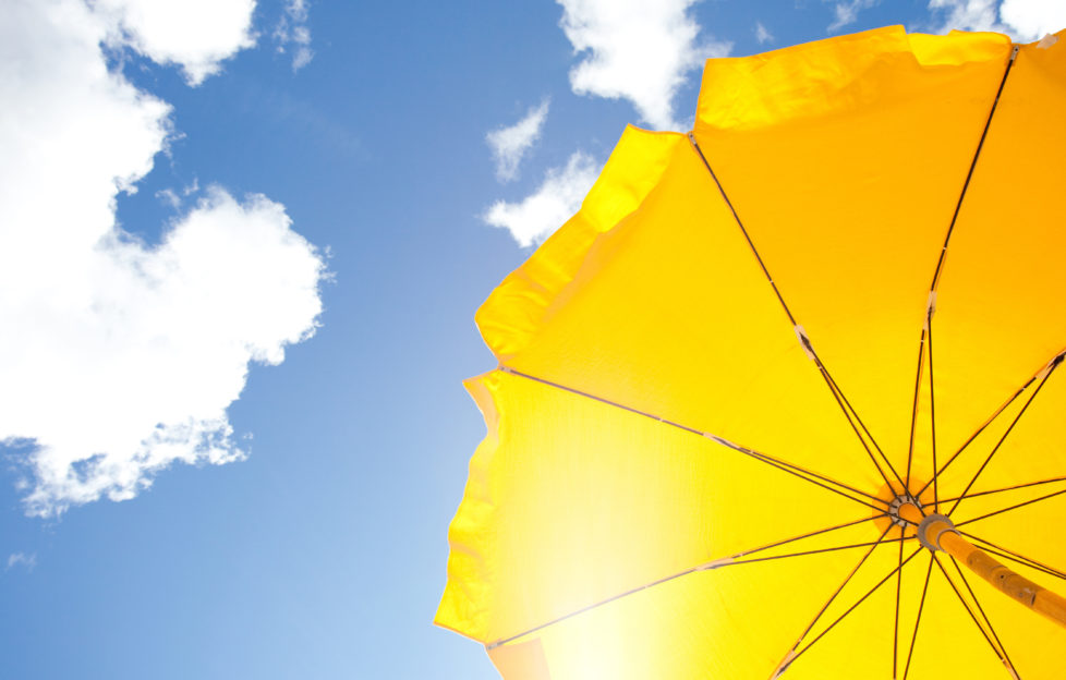 yellow umbrella on blue sky with clouds;