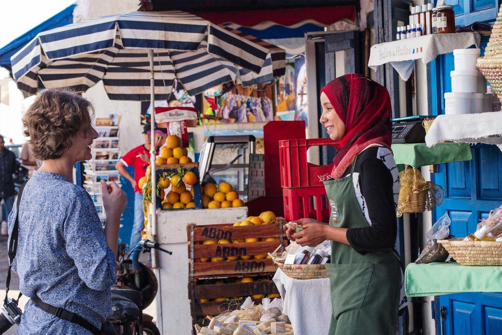 Woman tourist chatting to stallholder in Moroccan market, Rabat