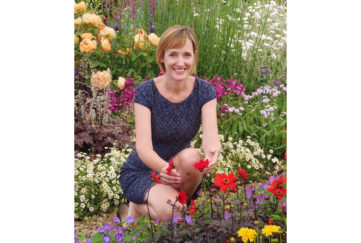 Sarah Squire, chair of Squires garden centres, kneeling amid colourful mixed flower border