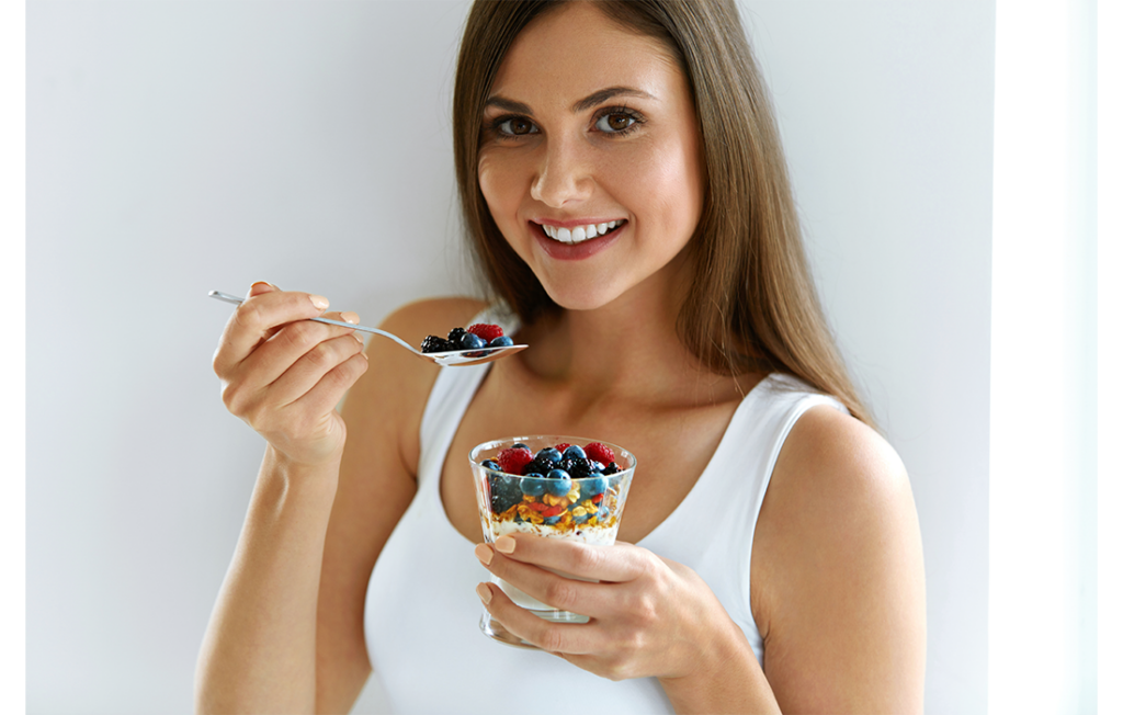 Young woman eating granola and berries breakfast