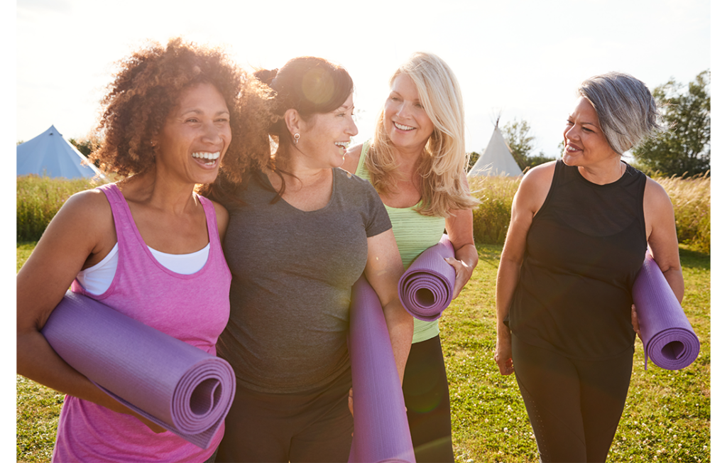 Four women outdoors in park with yoga mats