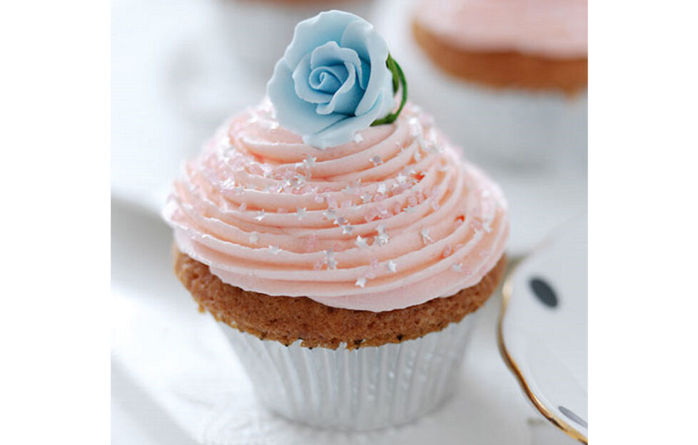 Cupcake with swirl of pink icing and blue sugar rose, friendship cake