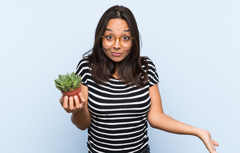 Young brunette woman holding a plant with shocked facial expression; ne
