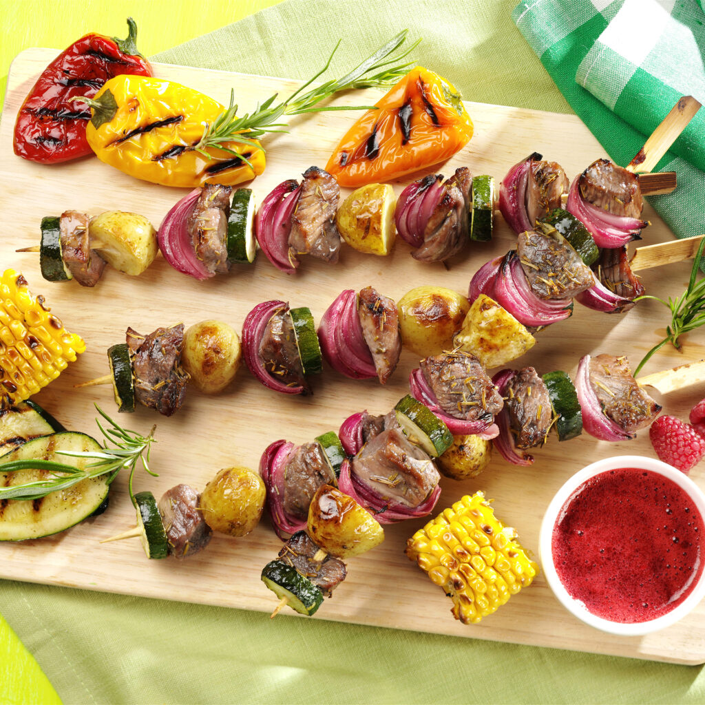 Lamb and red onion kebabs on a wooden board, char grilled veg around
