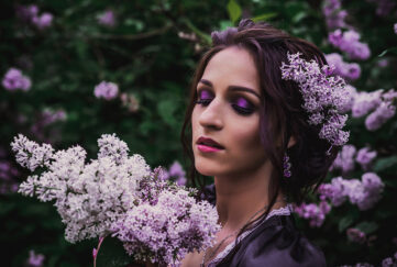 Lady in black and purple baroque dress smelling lilac blossom at dusk
