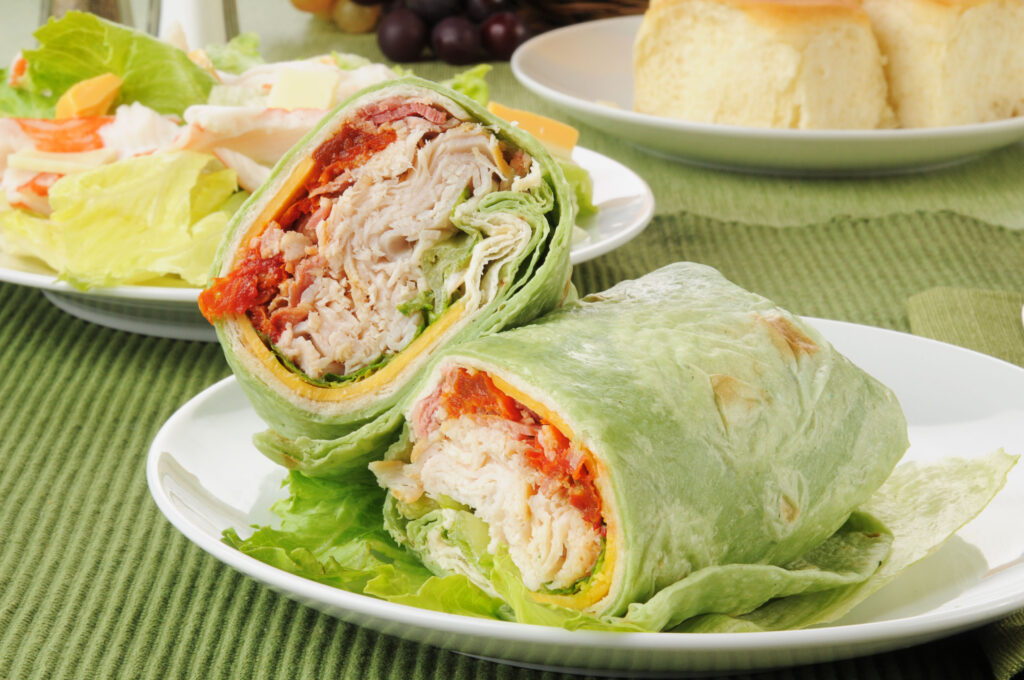 A turkey club sandwich in a spinach tortilla with crab salad;