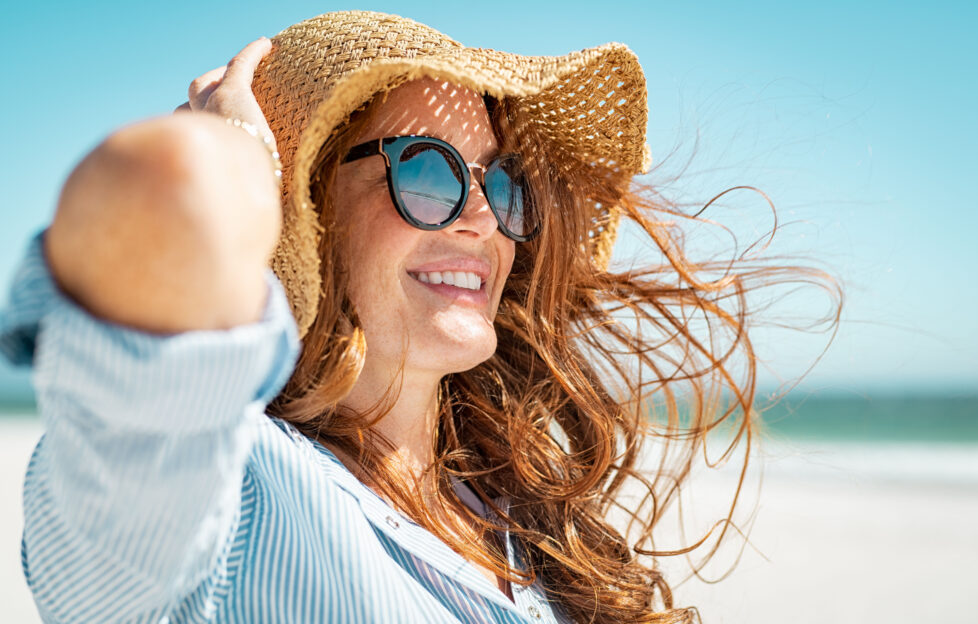 Side view of beautiful mature woman wearing sunglasses at beach. Young smiling woman on vacation looking away while enjoying sea breeze wearing straw hat. Closeup portrait of attractive girl relaxing.;