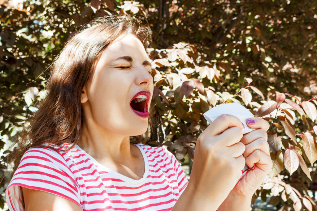 Front view of a single girl sneezing and blowing in a wipe outdoors with a green background.;