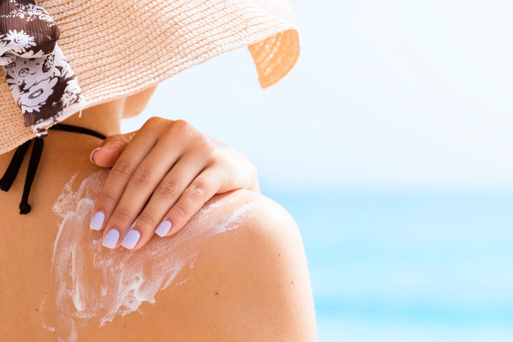 Sunscreen sunblock. Woman in a hat putting solar cream on shoulder outdoors under sunshine on beautiful summer day.;
