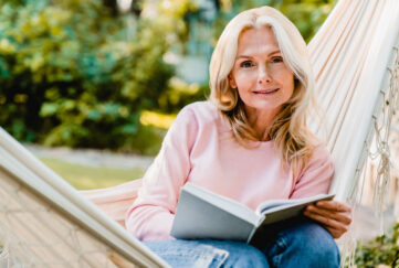 Nice-looking mature blonde woman resting in hammock in the garden with a book;