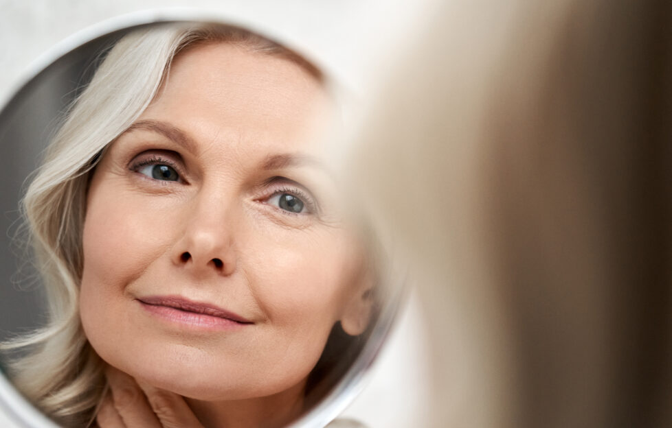 Happy 50s middle aged woman model touching face skin looking in mirror reflection. Smiling mature old lady pampering, healthy moisturized skin care, aging beauty, skincare treatment cosmetics concept.;