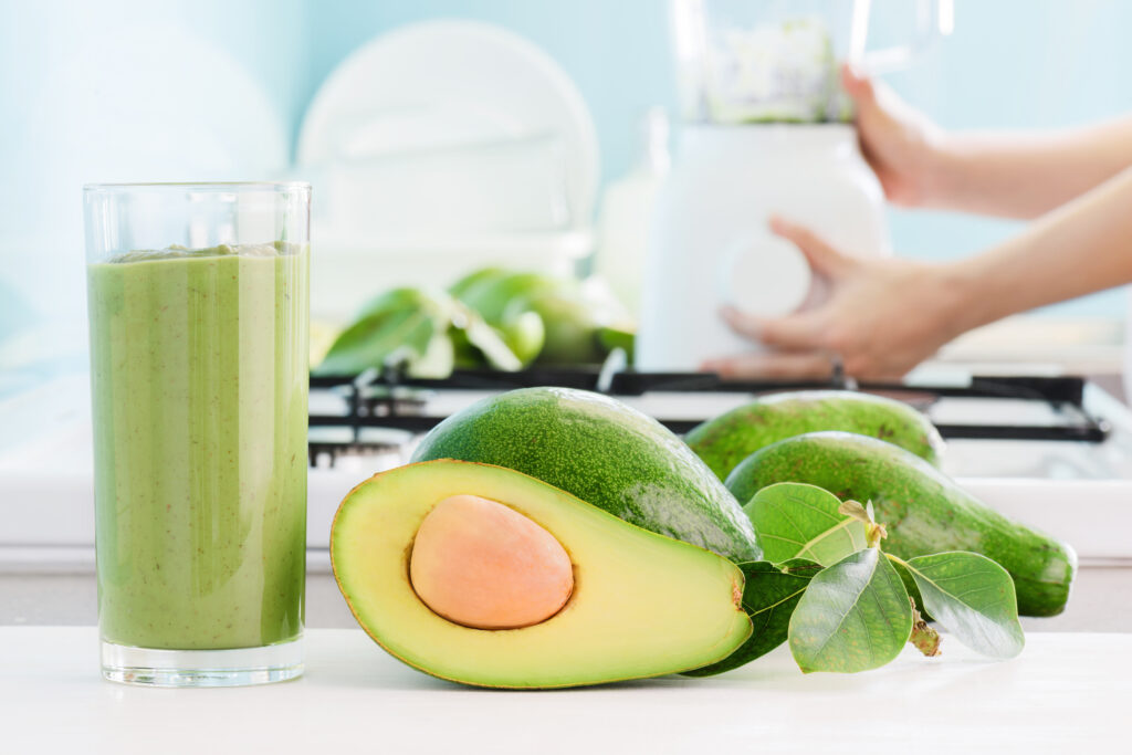Fresh avocado smoothie and ripe green avocados on kitchen table. Hands of woman using blender are visible in background. Healthy eco food and natural drink.;