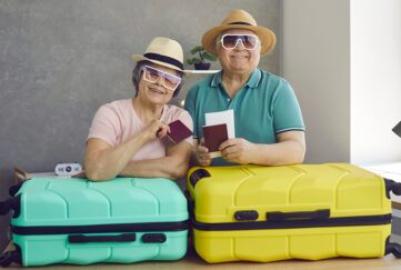 Mature husband and wife at home before going on family holiday. Portrait of happy cute active senior couple with flight tickets, passports and suitcases standing in living-room and smiling