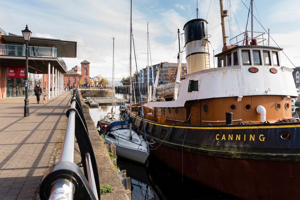 Tug boat moored at harbourside, brick building with tower in background