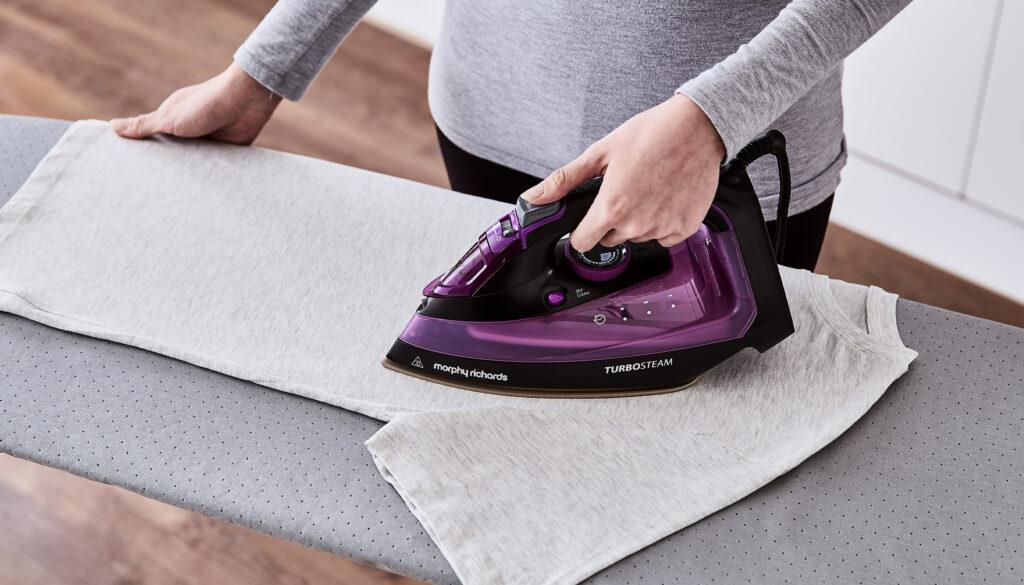 Close up of woman ironing T shirt