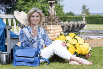 Anthea Turner sits on grass by a fountain with a glass of champagne and large blue Chrysanthea hadbag