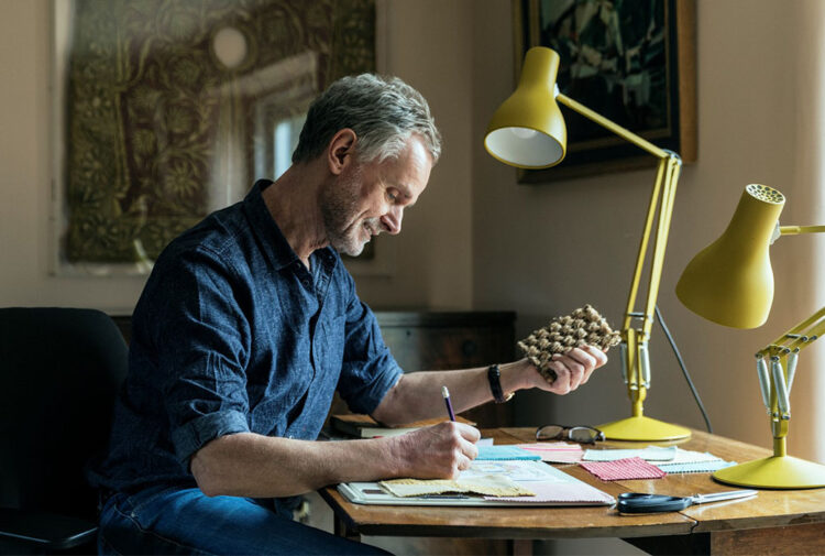 Mature man sitting ar desk writing, holding small square of natural flooring