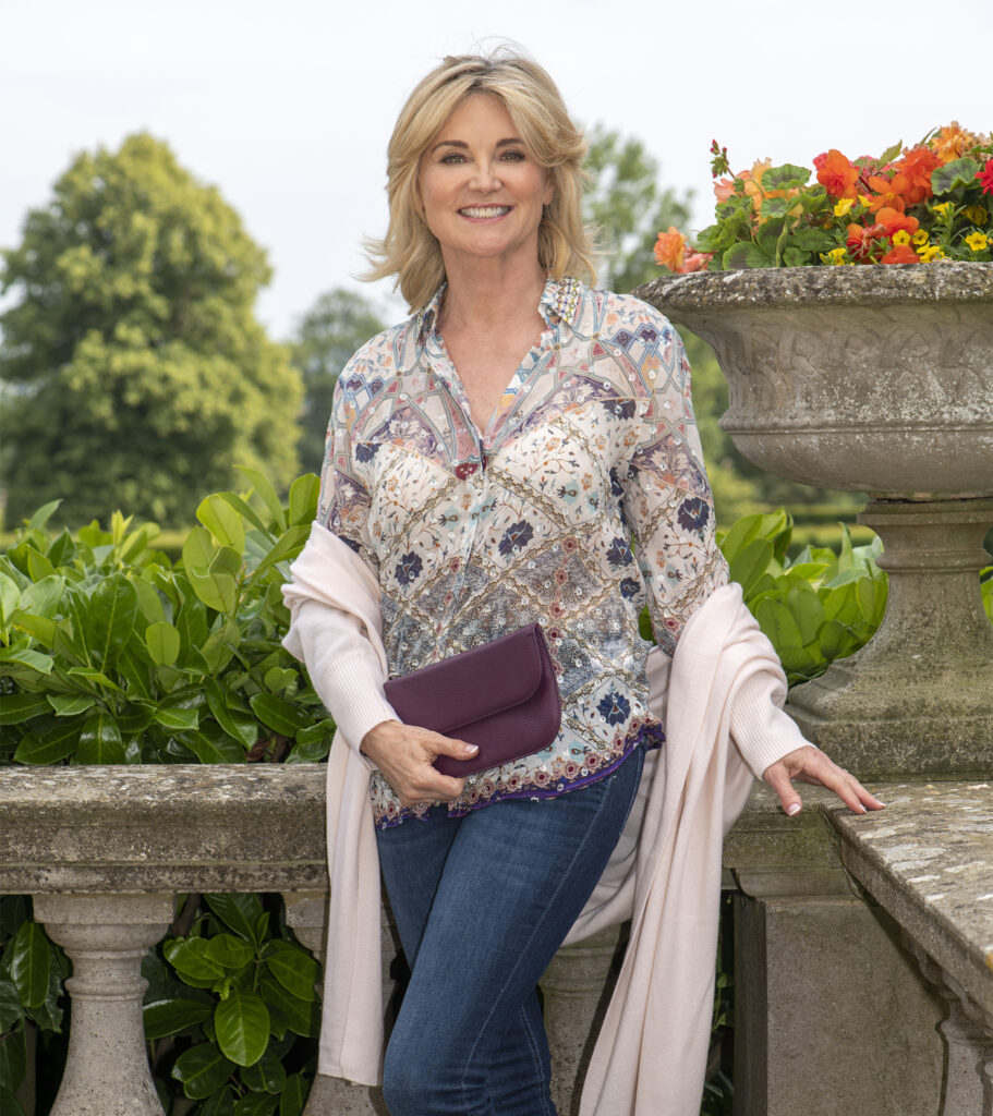 Anthea Turner by stone balustrade with purple clutch bag
