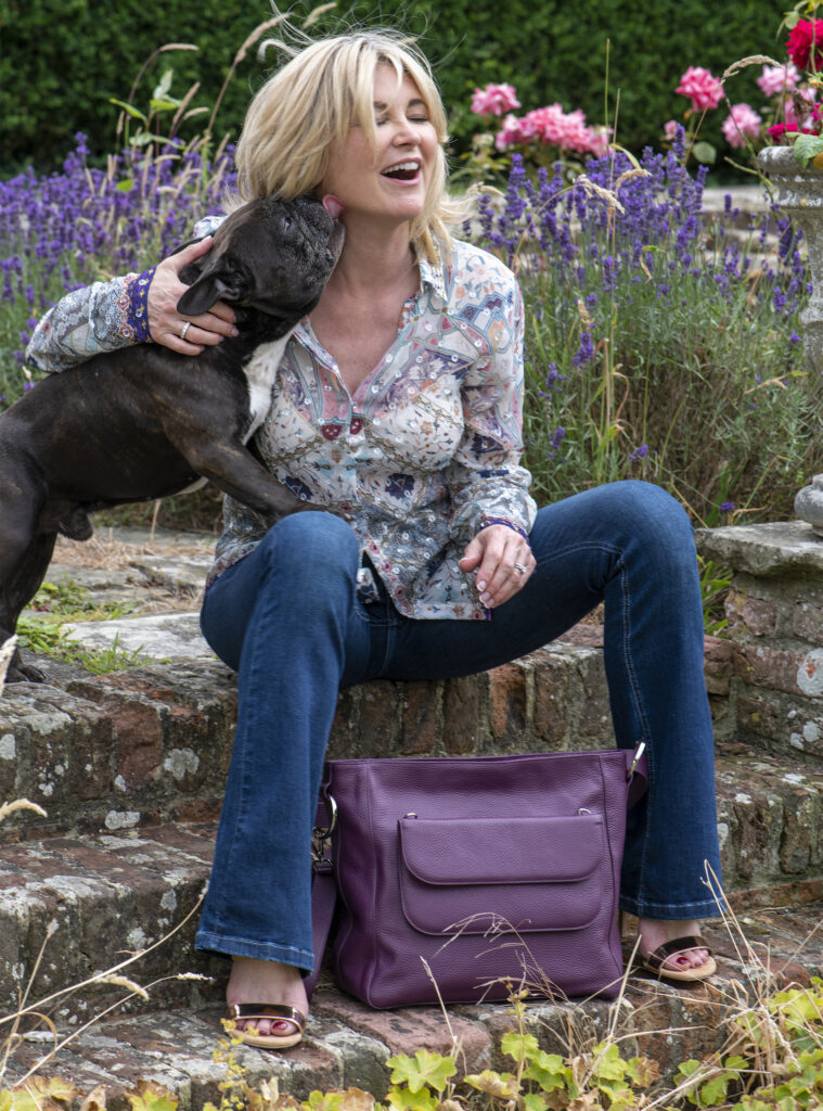 Anthea Turner sits on stone steps, her French bulldog Soho licking her face, purple Chrysanthea bag at her feet