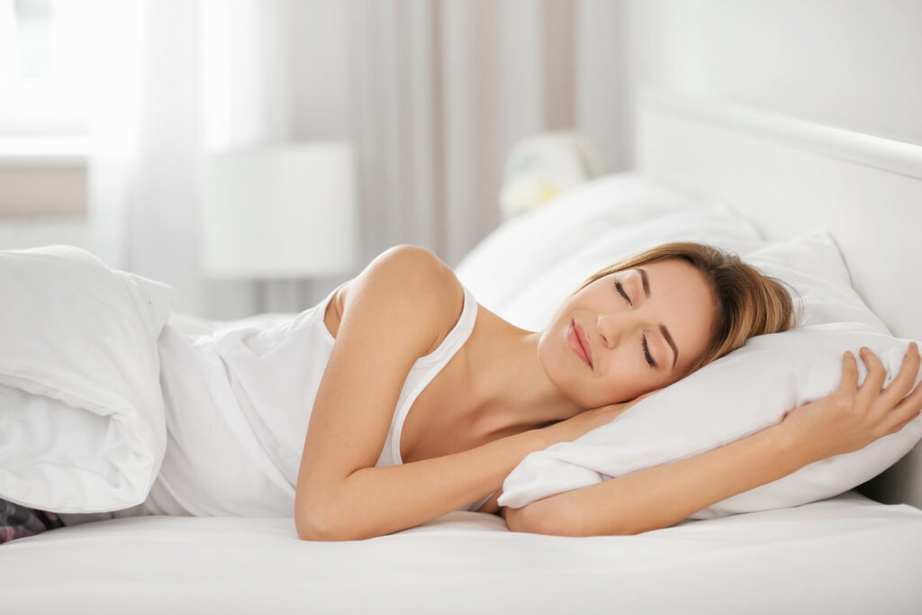 Young woman sleeping on white pillow in bed;