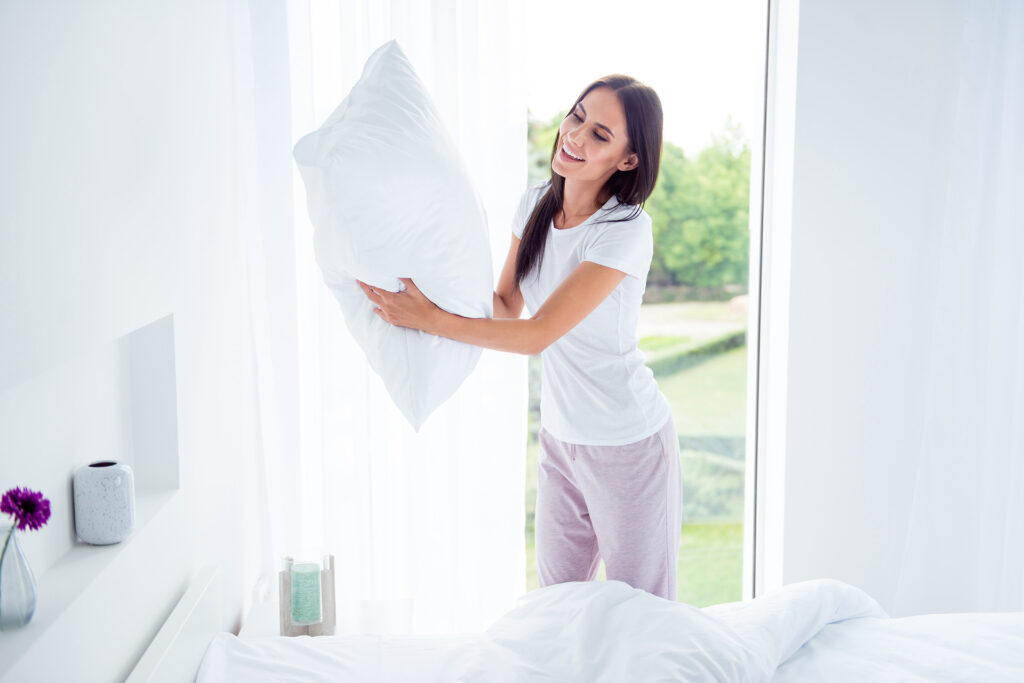 Daily home work routine. Charming beautiful nice stylish brunette girl doing everyday house work, householding, changing fresh case, linen in modern light white interior room,