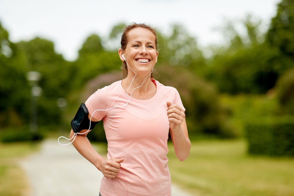 fitness, sport and healthy lifestyle concept - smiling woman with earphones wearing armband for smartphone, jogging at summer park and listening to music;