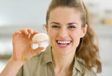 Happy young housewife holding mushroom in kitchen;