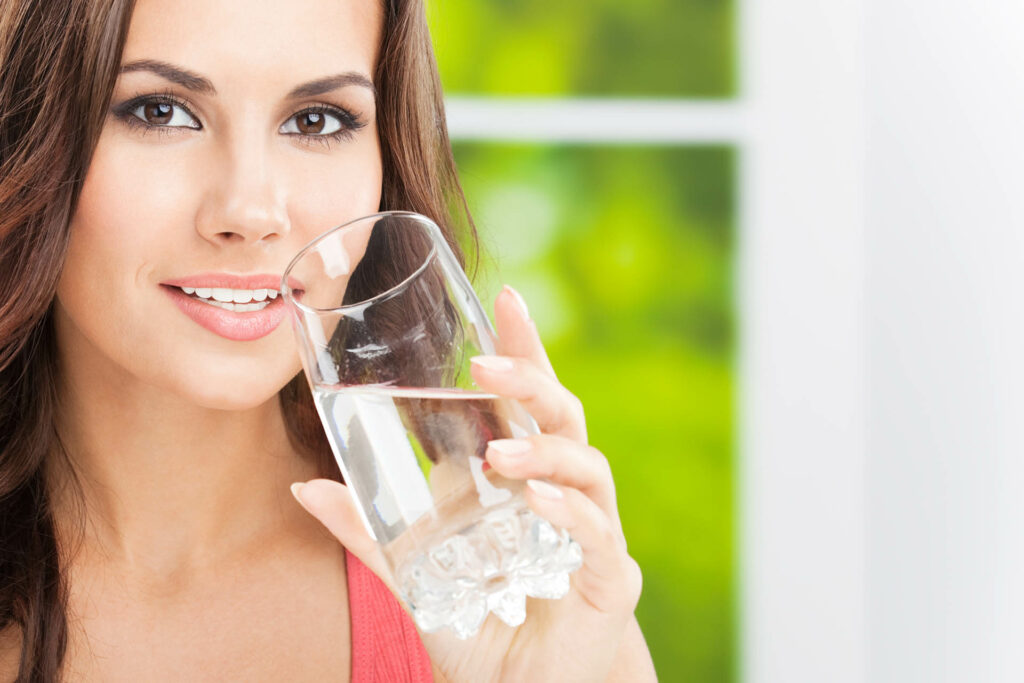 Portrait of young woman drinking water, outdoor, with copyspace;