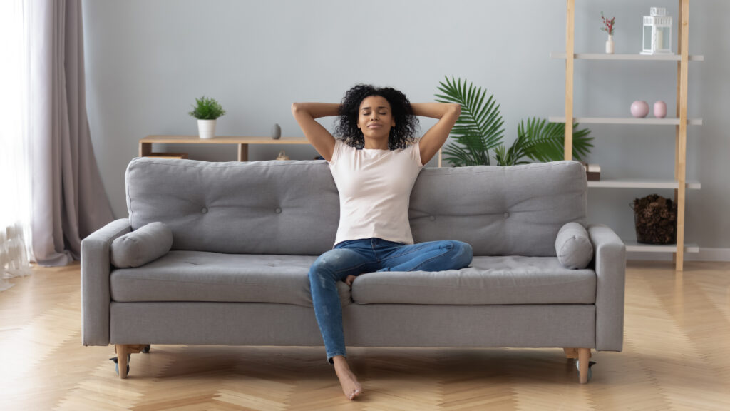 Young calm black woman relaxing sit on comfortable sofa in modern living room, lazy happy african woman girl resting on couch breathing fresh air enjoy peace of mind no stress free on couch at home;