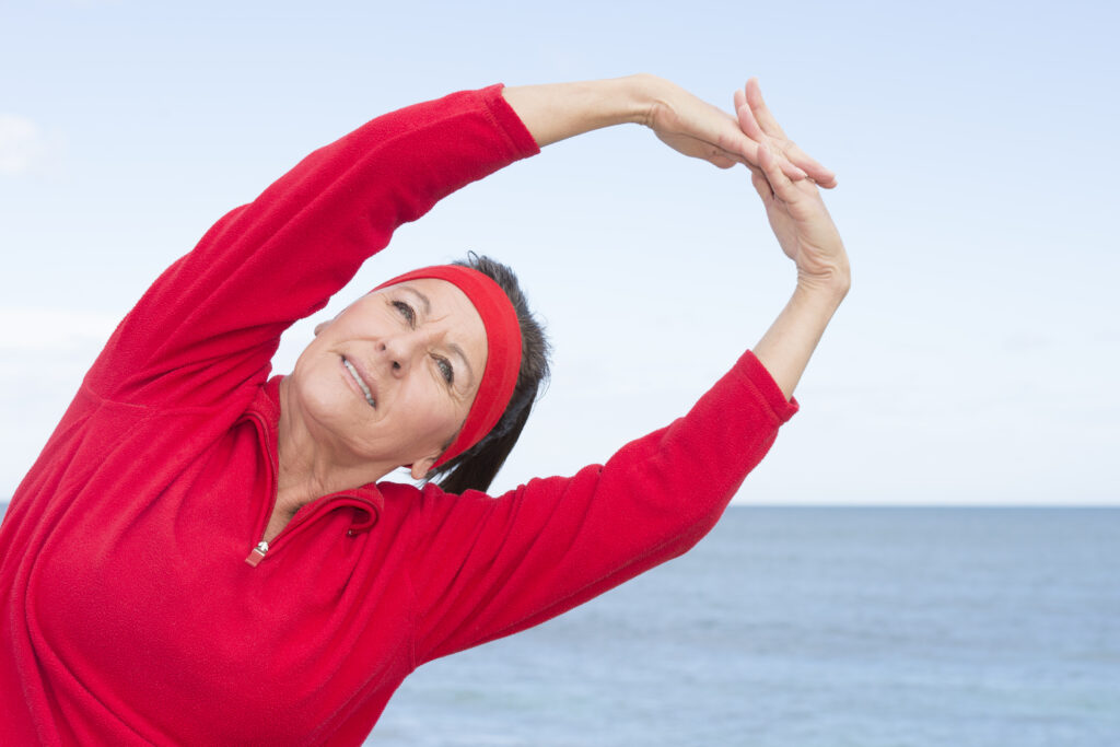 Portrait attractive mature woman showing active retirement, exercising with weights arms up outdoor, positive, confident, energetic, focused, with cloudy sky as background and copy space.