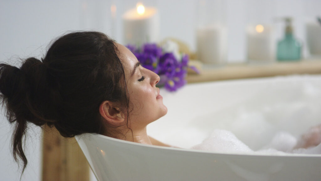 Brunette relaxing in foam bath with candles in background