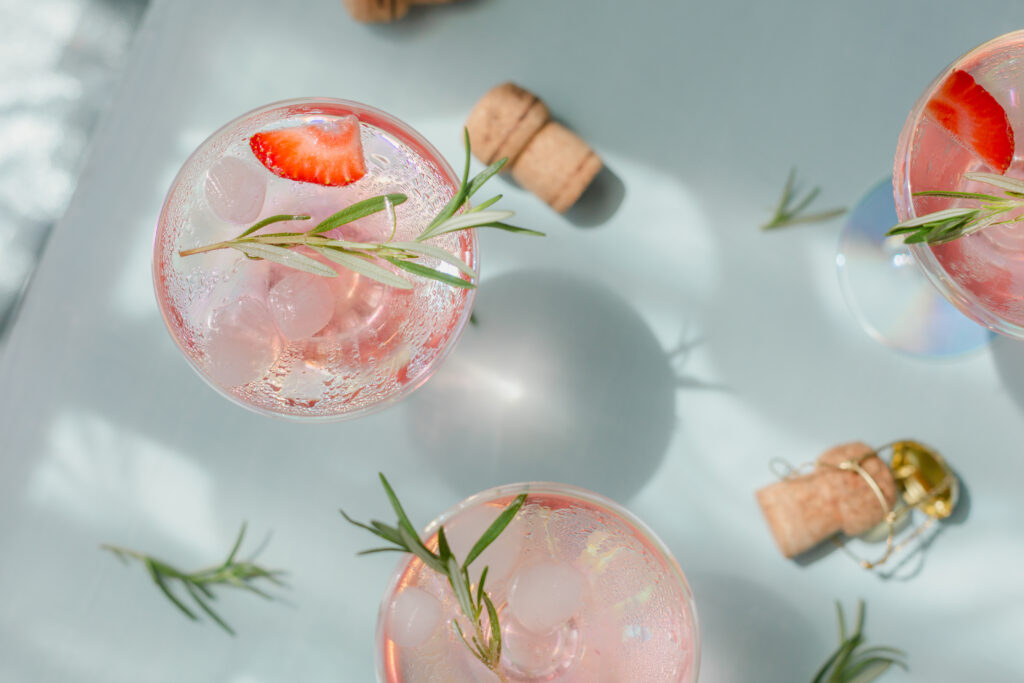 Summer drink with white sparkling wine. Homemade refreshing fruit cocktail or punch with champagne, strawberries, ice cubes and rosemary on light blue background.;
