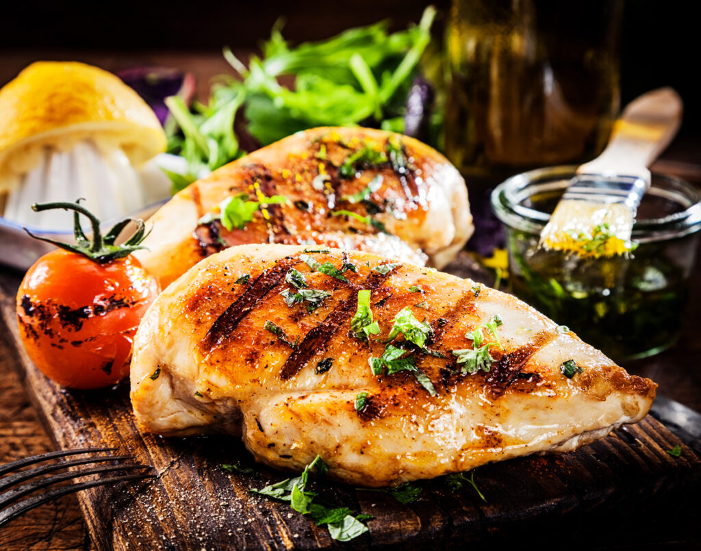 Marinated grilled healthy chicken breasts cooked on a summer BBQ and served with fresh herbs and lemon juice on a wooden board, close up view;