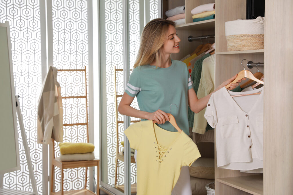 Young woman putting clothes into wardrobe at home;