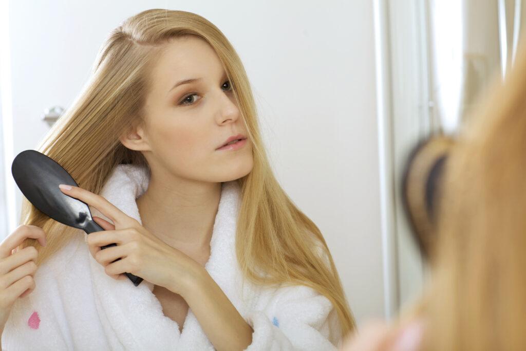Woman brushing hair;