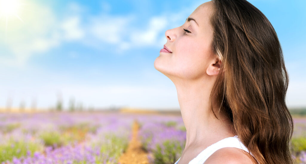 Woman taking deep breath with fields of flowers in background