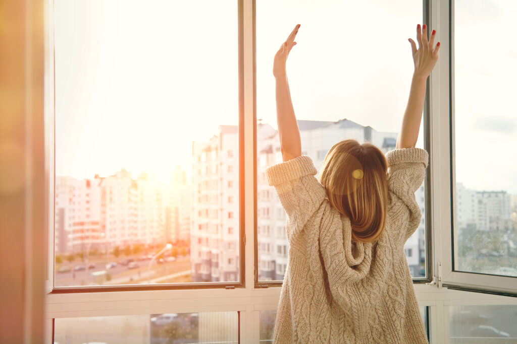 Woman near window raising hands facing the sunrise at morning