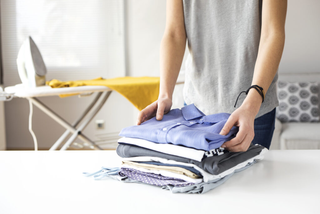 Ironing clothes on ironing board;